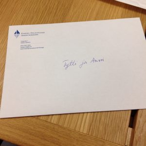 """valkoinen seurakunnan logolla varustettu kirjekuori, jossa lukee päällä """"Tytti&Anssi"""""""