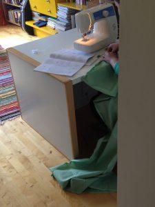 Kuvassa pöydänkulma ja osa ompelukonetta, lattialla mintunvihreää kangasta.