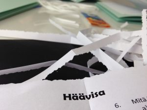 """Kuvassa leikattua paperisilppua, yhdessä kappaleessa lukee """"häävisa""""."""