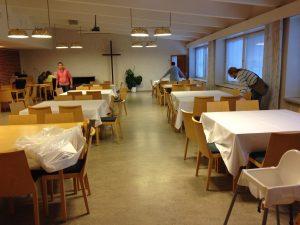 Meilahden kirkon seurakuntasali, jonka pöydille asetellaan valkoisia liinoja.